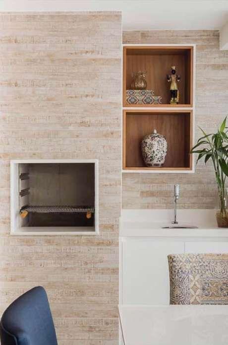 Churrasqueira feita de porcelanato amadeirado, parede da pia revestida com o mesmo material, armário e pia brancos.