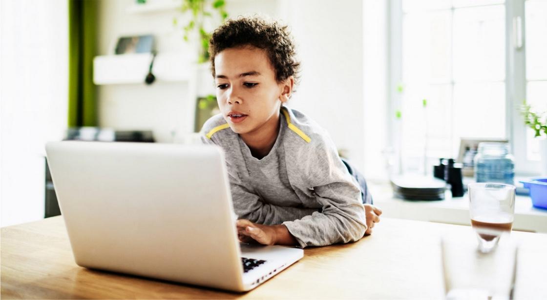 [alt: Ein Junge sitzt mit einem Notebook an einem Tisch.]