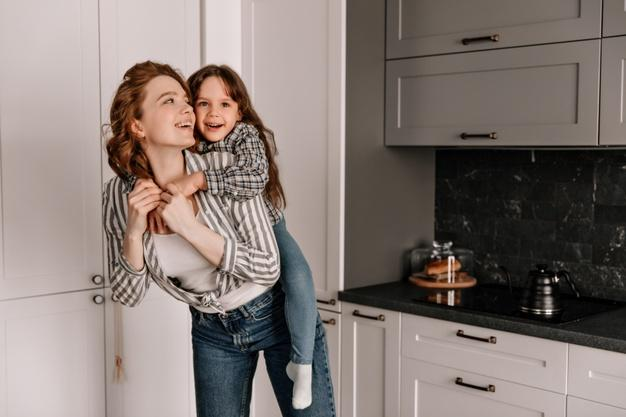 Merry mom and daughter in similar outfits play in kitchen and laugh. Free Photo