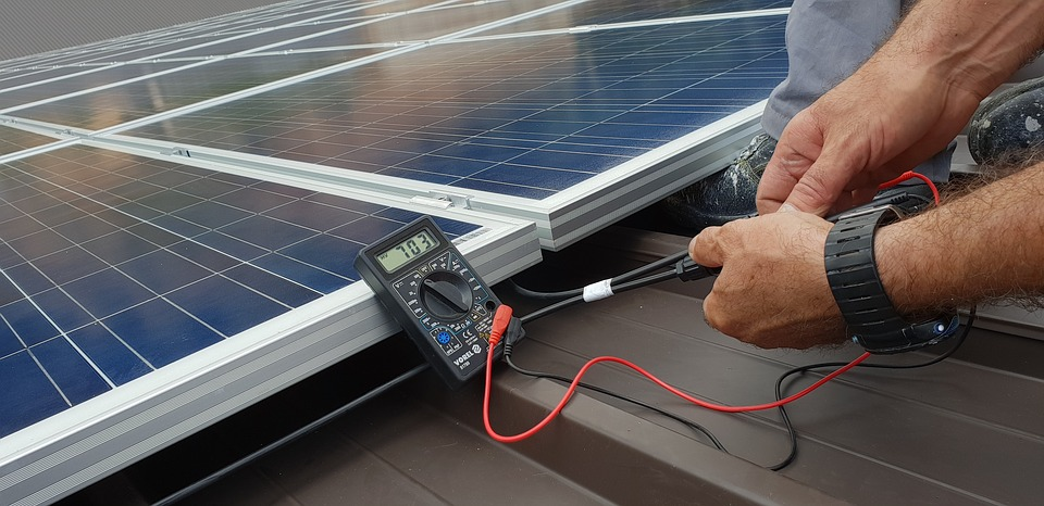 Installateur réglant les panneaux solaires sur la toiture d'une maison