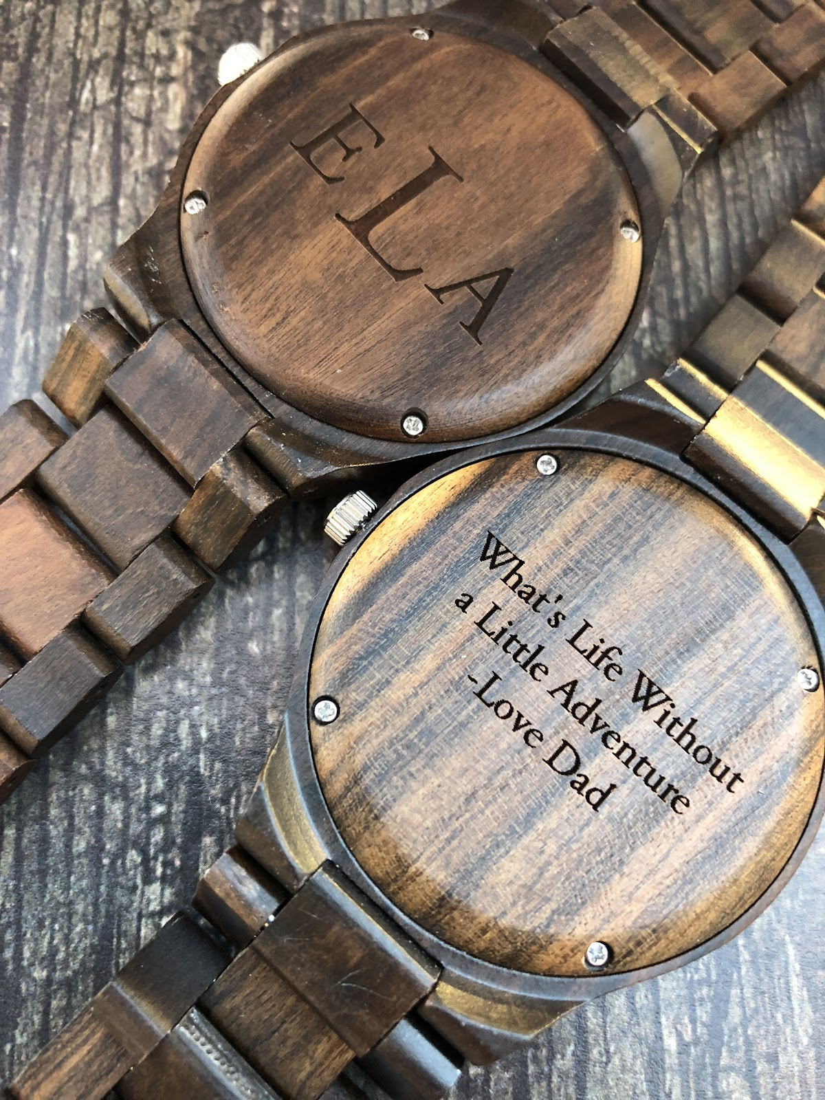 "Darrk brown wooden watches engraved with the initials E L A and a quote that says ""What's Life Without a Little Adventure, Love Dad""."