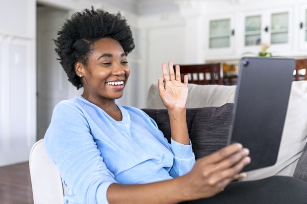 woman smiling waving in front of her tablet, in an online meeting