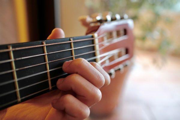 La mano de un niño haciendo el acorde D7 en una guitarra con cuerdas de nylon