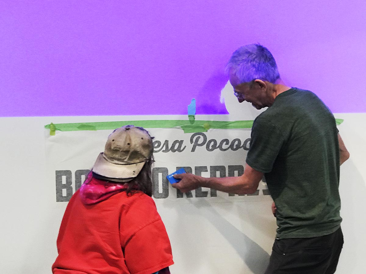 Teresa watches as Billiam James applies graphic lettering to the gallery wall at 312 Main on July 21, 2019. Photo by Franke James.