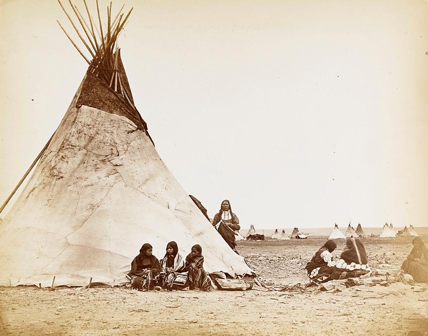 Campo della tribù Arapaho. Da notare l'uomo col pettorale vicino al tepee con in mano il tomahawk-pipa.