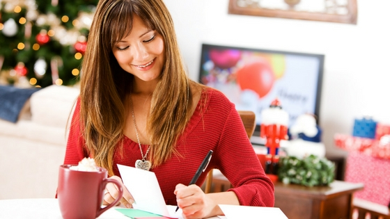a woman writing in a greeting card