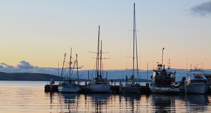 Sailboats docked on the serene sunset waters of Hobart Harbour in Tasmania