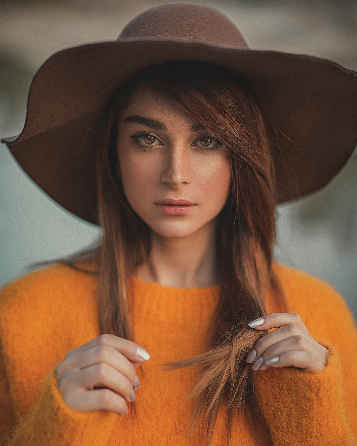 headshot of woman wearing brown hat and orange sweater