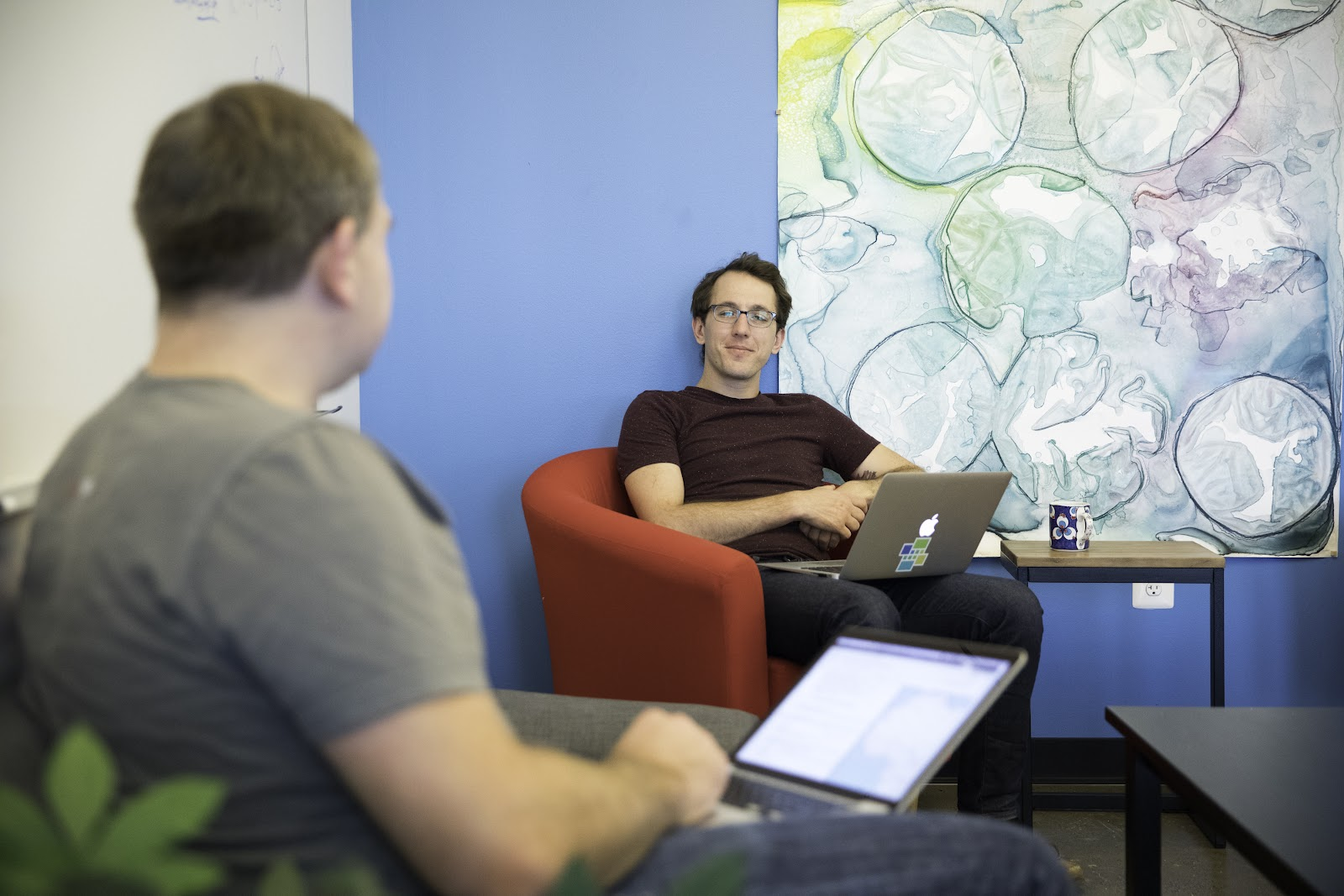 Two male colleagues sitting with computers in front of art work