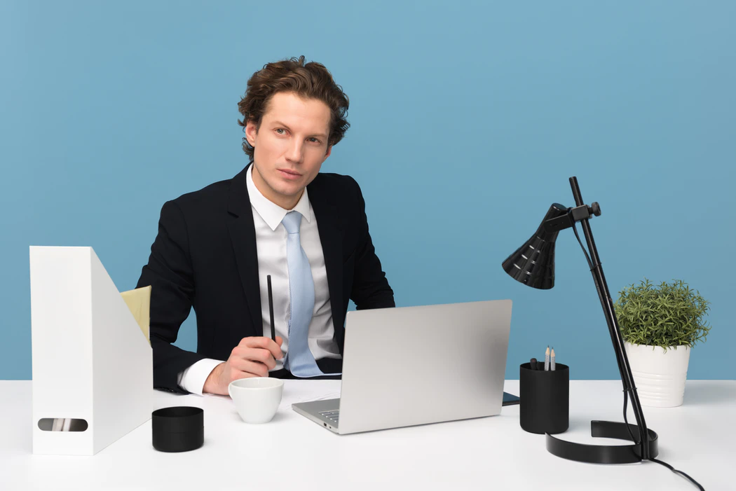 a smart man in a suit with a blue tie, is sitting in a modern office. On his white desk is a silver laptop, a black lamp, a plant in a white pot, he is holding a black pen and has a white mug next to him. He looks like a professional.