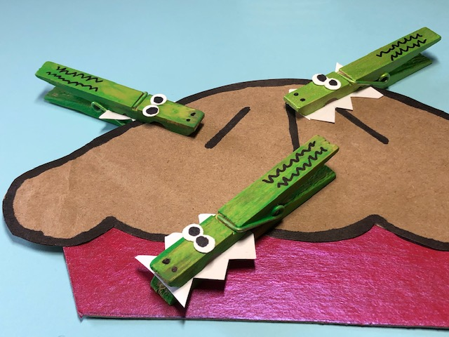 This is a photo of an example of an Alligator Pie craft, which includes painted alligator clothes pins clipped onto a paper pie.