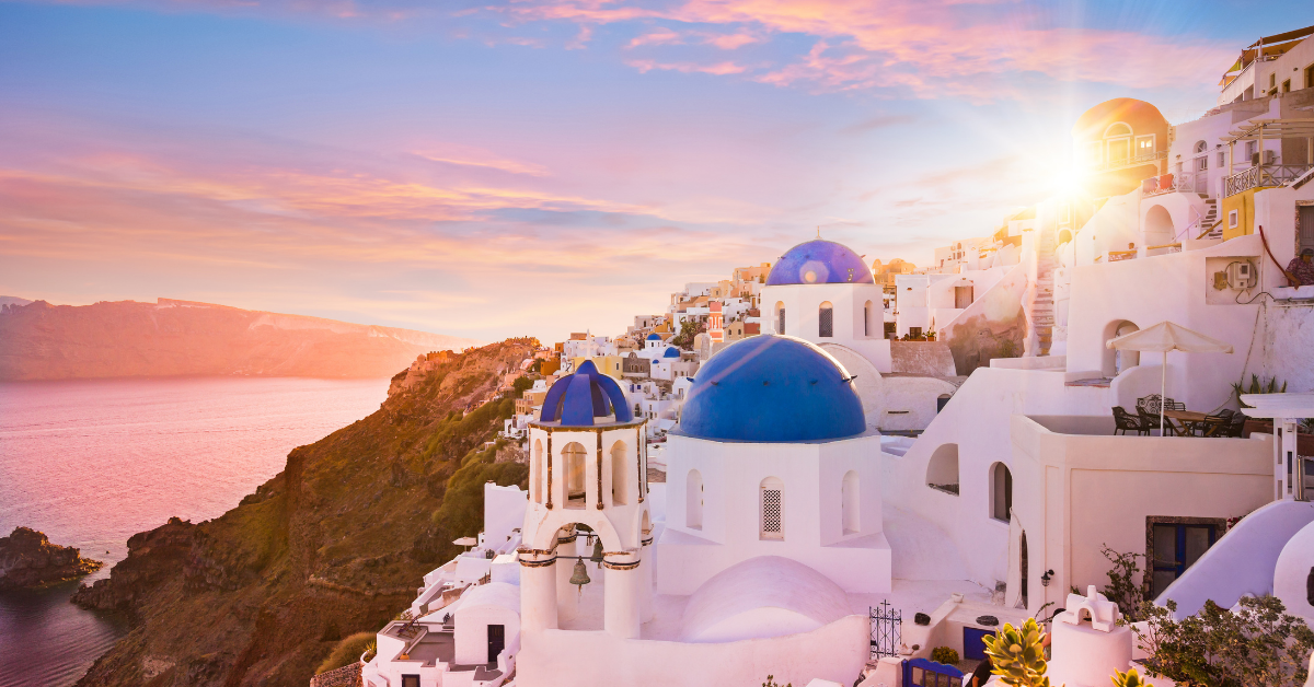 A pink sunset, white and blue houses and santorini