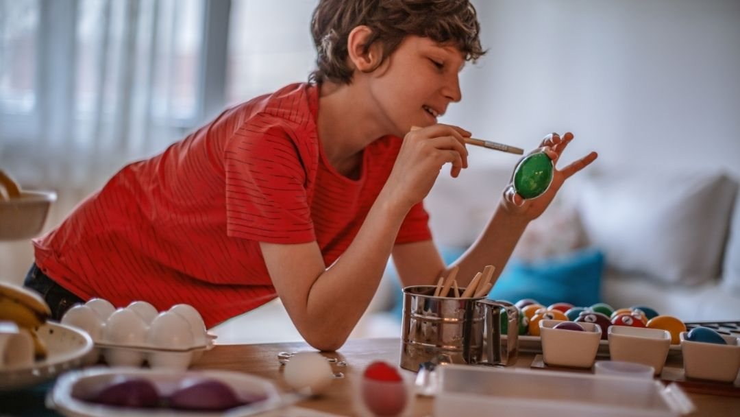 boy in a red tee shirt decorating Easter eggs - Holy Week for Kids