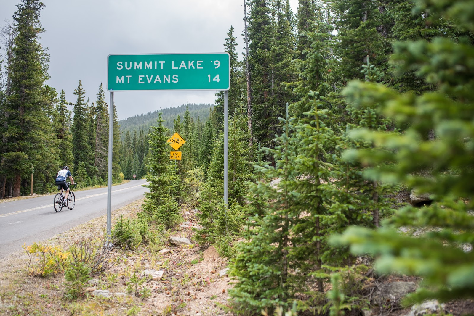 Cycling past road sign on Mt Evans Road Rocky Mountains
