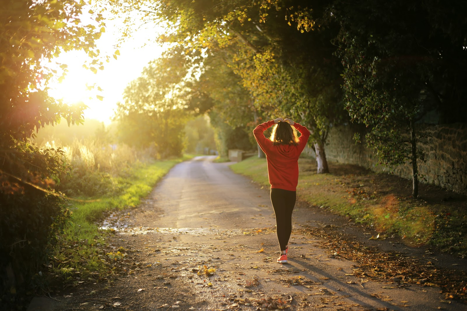 a woman in the park in a red jogging outfit in the sun