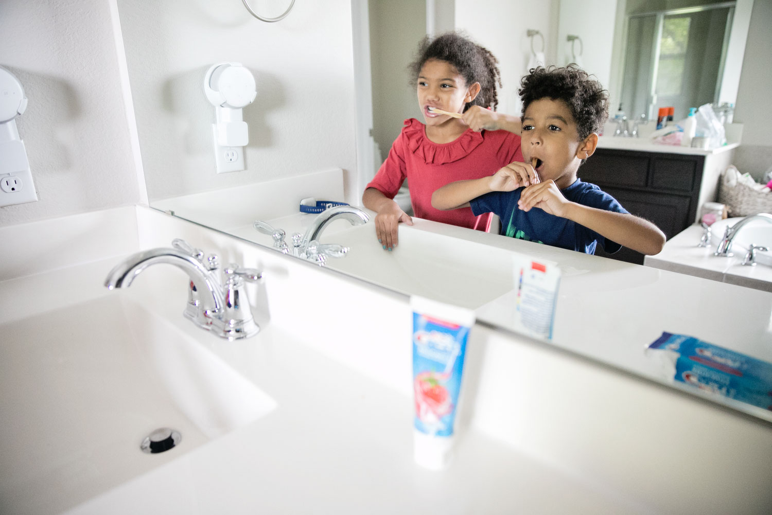 This is our mission to find the best kids toothpaste. Little girl and little boy brushing their teeth while looking in the mirror.