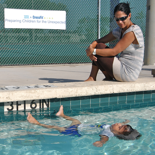 mother watching son float in the pool