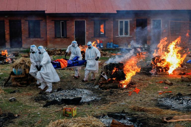 Members of the Nepali Army, wearing PPE, carry the body of a coronavirus victim at a crematorium in Kathmandu [File: Navesh Chitrakar/Reuters]