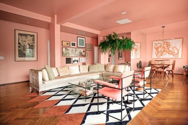 Sala com piso de madeira, sofá branco, poltronas rosa e paredes e teto com rosa predominante