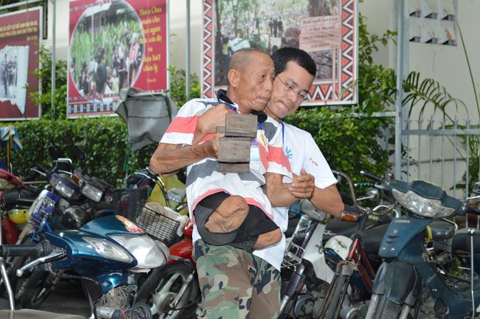 Tình nguyện viên giúp đỡ quý ông từ khu vực để xe vào trong sân tham dự Ngày tri ân