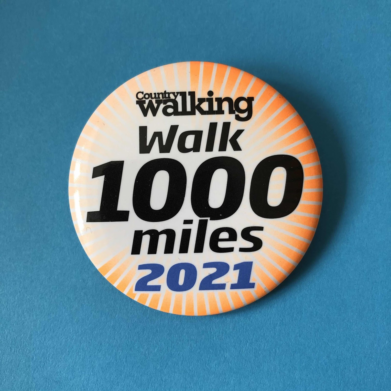 orange pin badge with Country Walking Walk 1000 miles written on it