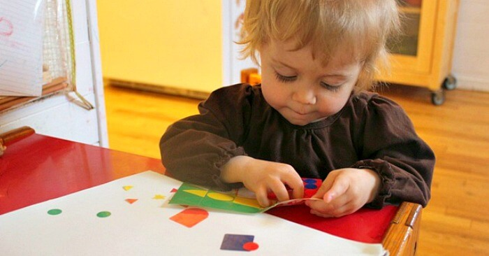 Toddler placing stickers onto white paper.