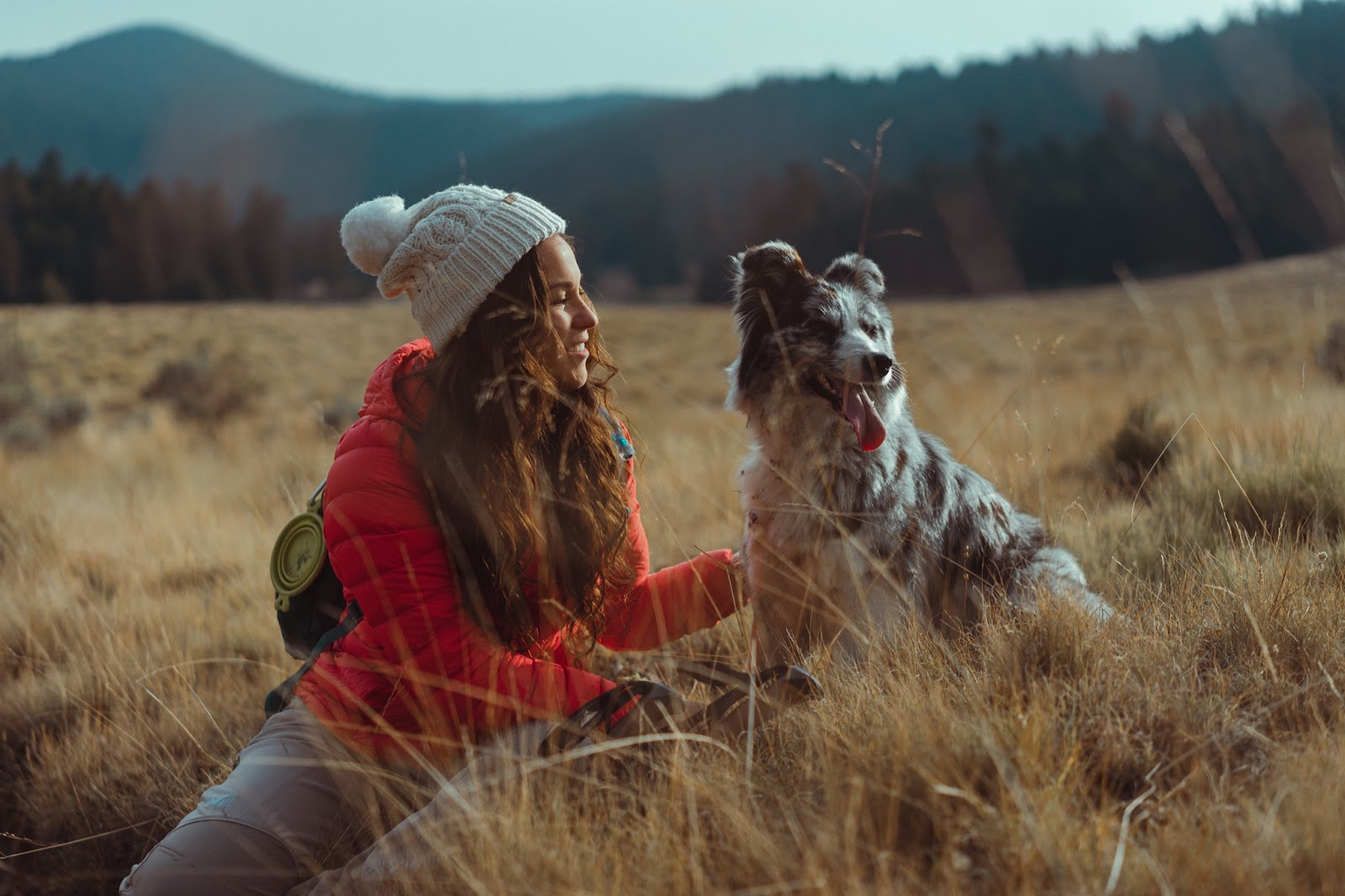 woman sitting in a field with her dog