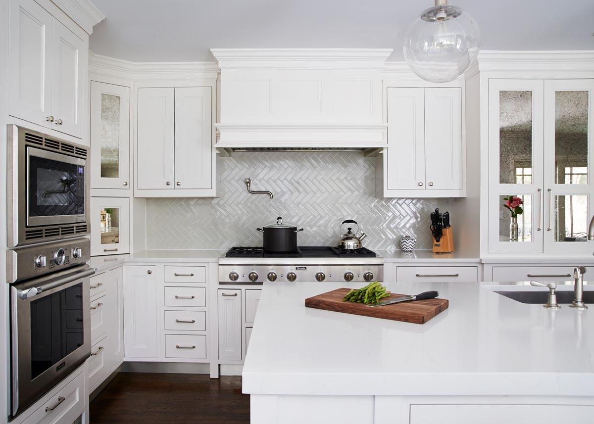 traditional white kitchen with white shaker cabinets and grey herringbone backsplash