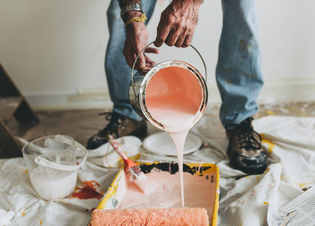 Person Holding Pink Paint Bucket Pouring on Black Container