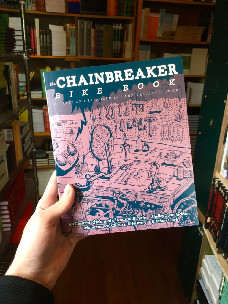 Photo of a hand holding the new edition of Chainbreaker Bike Book with bookshelves in the background