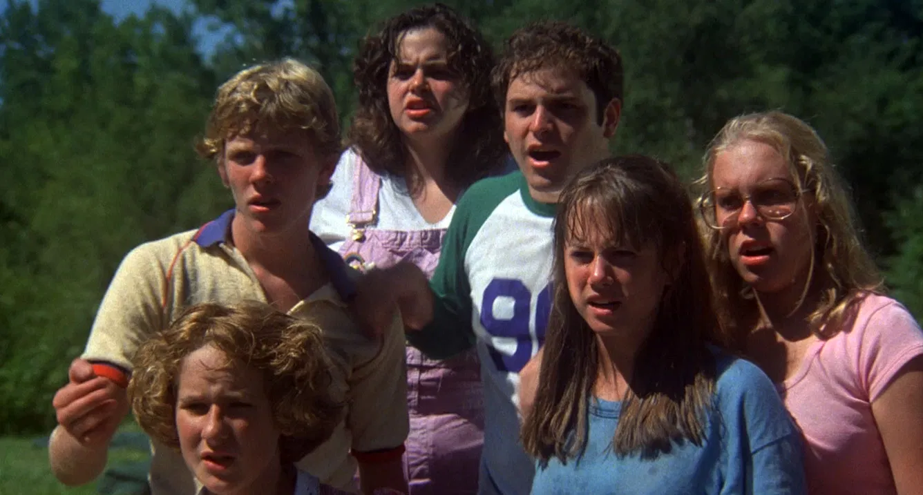 Still from The Burning (1981). A group of six teenage campers huddle together, all looking in the same direction with expressions of shock.
