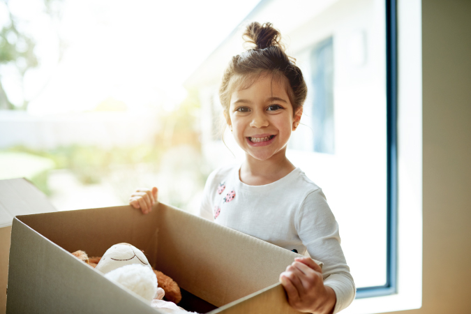 A little girl packing her toys in a moving box