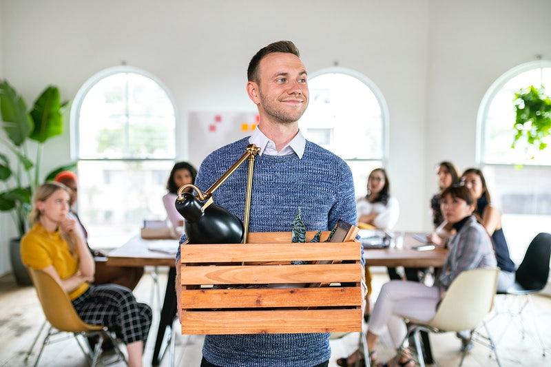 Um homem saindo de uma reunião com uma caixa na mão.