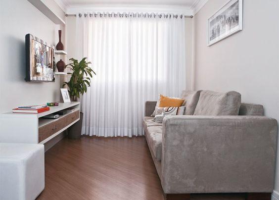 Sala com piso de madeira, sofá cinza com almofadas, hack branca e marrom e acessórios decorativos marrom.