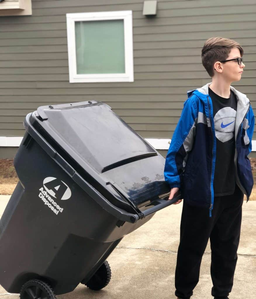 Age appropriate chores for 10-12 year olds: Photo of tween boy taking out the garbage