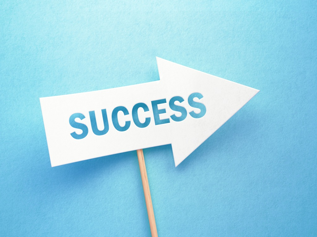 Arrow shaped success sign on a stick, over blue background