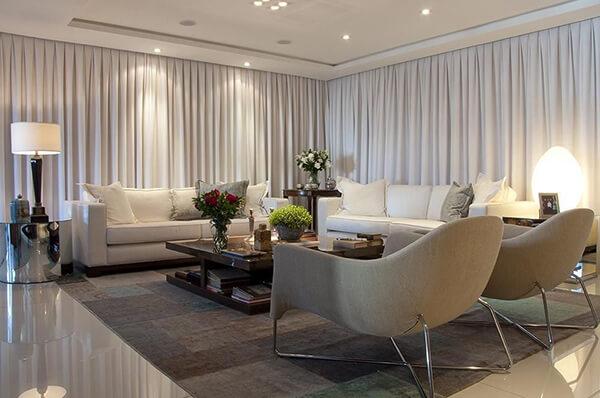 Vista lateral de uma sala ampla, com dois sofás brancos de 3 lugares e duas poltronas arredondadas cinzas. A sala é cercada por cortinas, possui um tapete cinza no chão e uma mesa de centro de madeira. Imagem para ilustrar a reforma de casas.