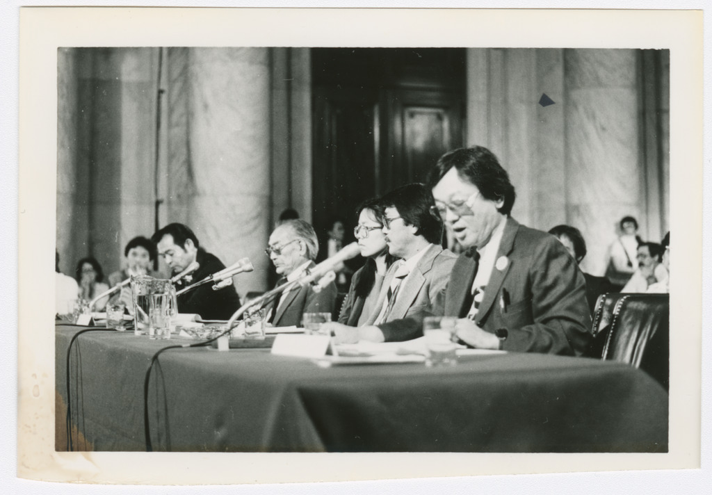 Several Japanese Americans seated at a table with microphones. Closest to the camera is William Hohri, who is reading a written statement into a microphone.