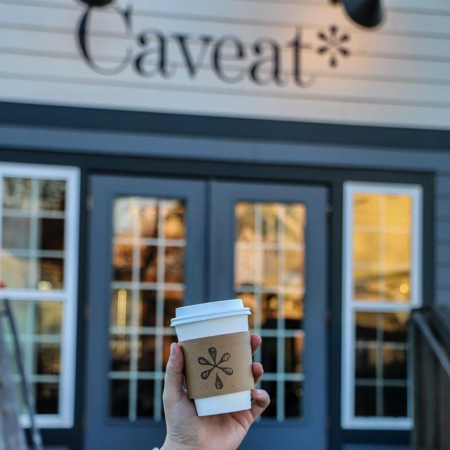 Hand holding a disposable coffee cup in front of Caveat Coffee in birmingham AL. How to find the best coffee in Birmingham AL