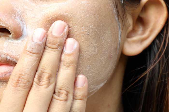 woman using exfoliator skincare at home
