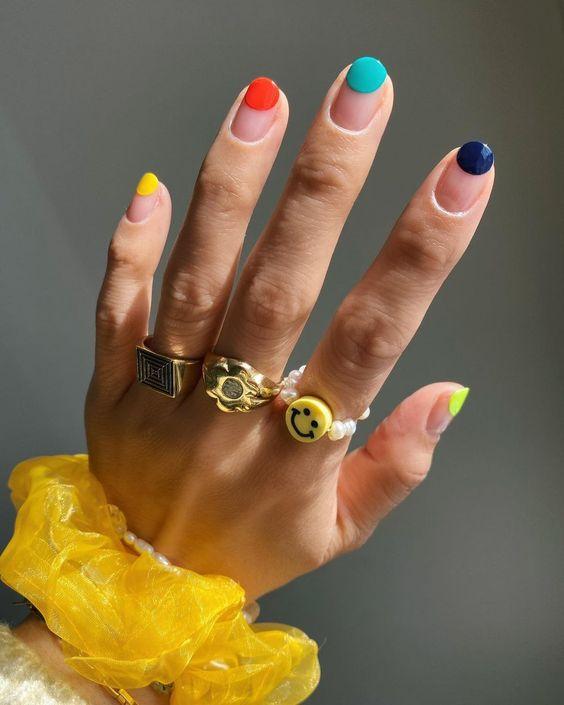 Mão com aneis dourados, pulseira amarela e unhas pintadas com bolas coloridas. Foto: Pinterest. Post: Nail art fáceis para fazer em casa