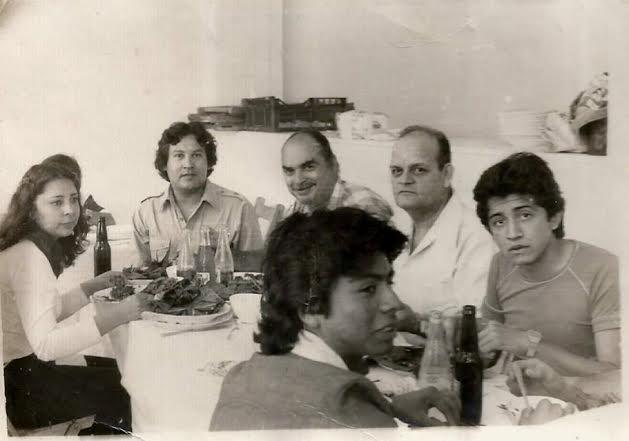 Foto en blanco y negro de un grupo de personas sentadas en una mesa  Descripción generada automáticamente