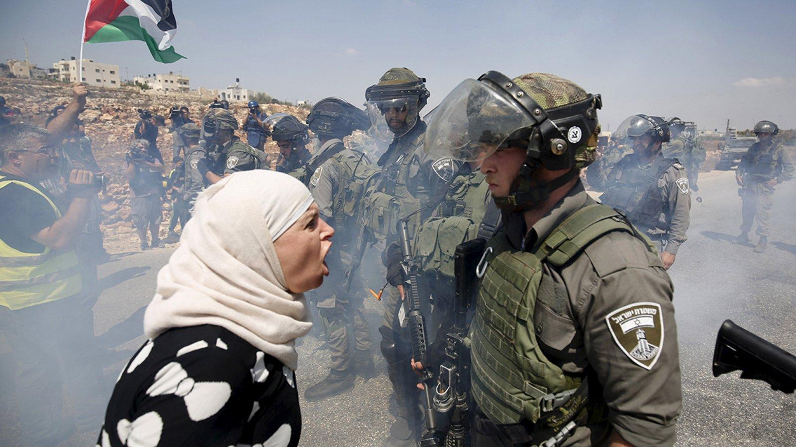 A Palestinian woman argues with an Israeli border policeman in the West Bank.