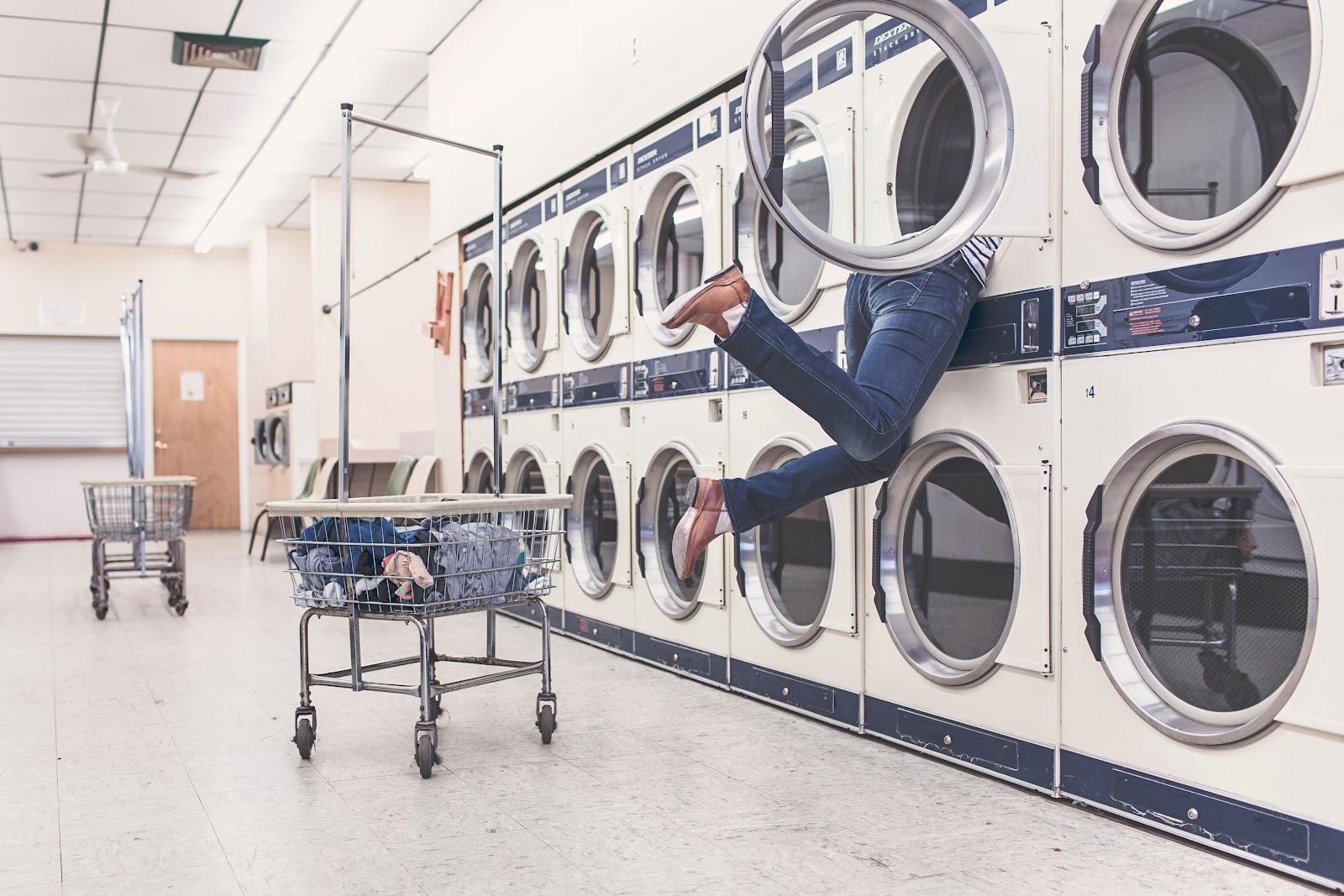 מכבסה גדולה, אישה נכנסת לתוך אחת ממכונות הכביסה