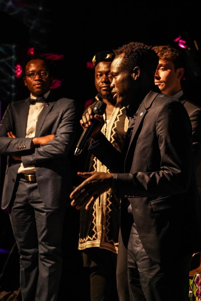 Mr. Joseph Okello, a man in a dark suit, is performing at the Davos Africa Night speaking about Refugee Camps