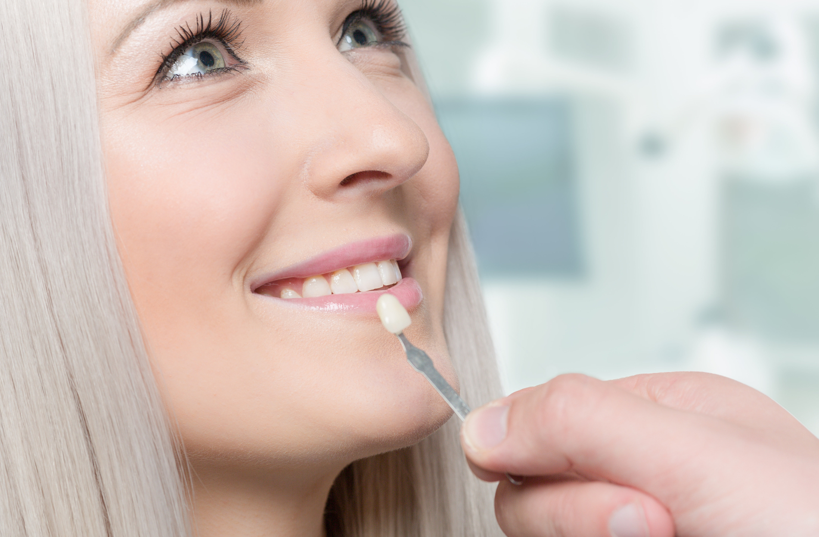 blonde woman smiling while the dentist checks if the veneers are the right colour