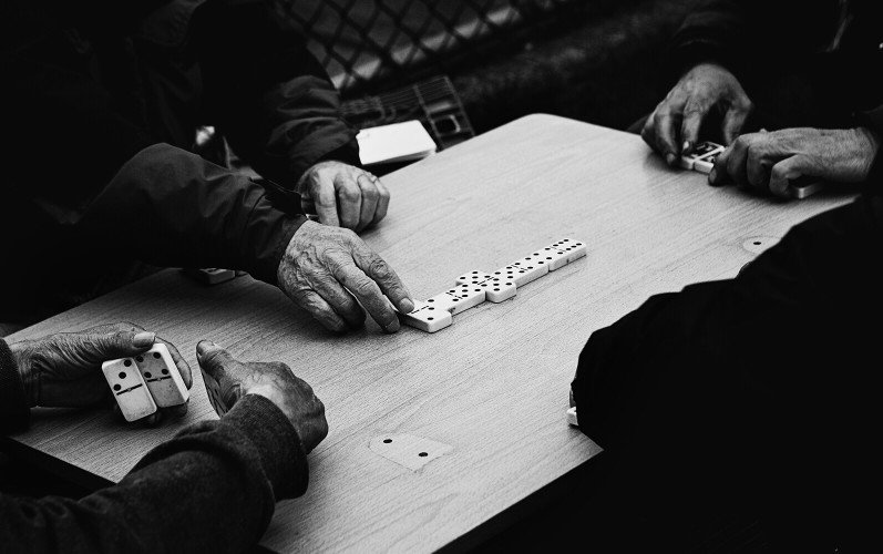 4 pairs of hands playing dominoes on a table. Picture is in black and white.