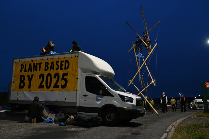 A van and a bamboo structure block the road