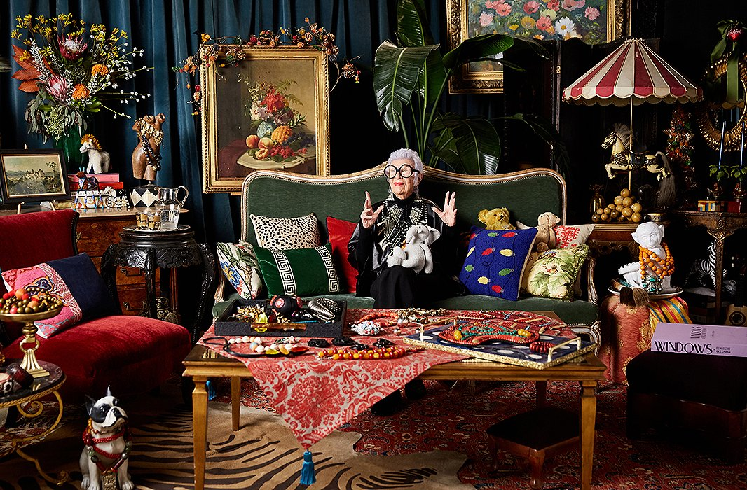 Iris in her lounge surrounded by eccentric ornaments, paintings, flowers and furniture