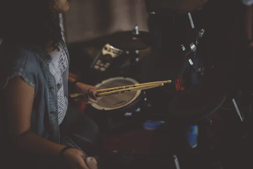 drummer sitting at drum kit holding drum sticks